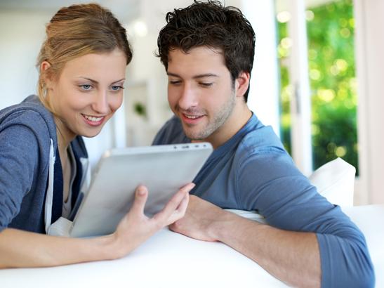 Couple faisant un devis immédiat de fenêtres sur mesure sur leur tablette